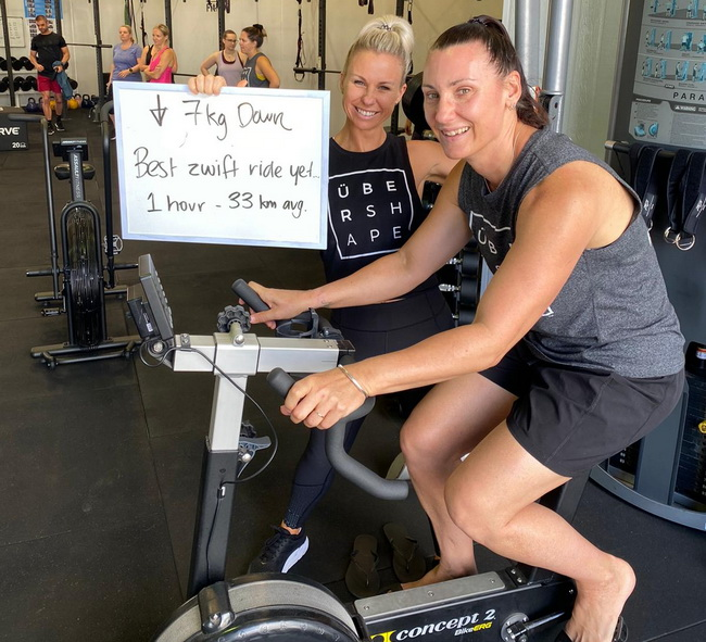 Bec on a stationary bike with coach Kylie next to her smiling and holding up a sign about having lost 7 kilos
